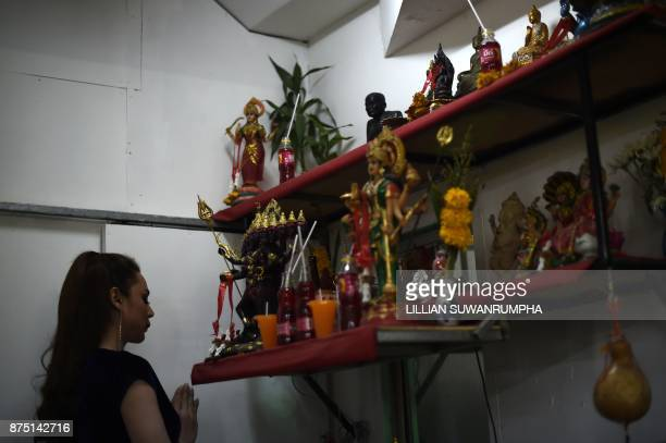 This photo taken on October 7 2017 shows a cabaret performer praying before a shrine with Hindu deities and Buddhist icons in the dressing room at...