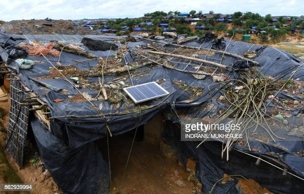 This photo taken on October 7 2017 shows a solar panel on the roof of a temporary home for Rohingya refugees at the Kutupalong refugee camp in Cox's...
