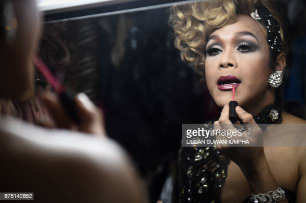 This photo taken on October 7 2017 shows a Thai cabaret performer applying lip gloss in the dressing room at ZAG bar a gay entertainment venue in...
