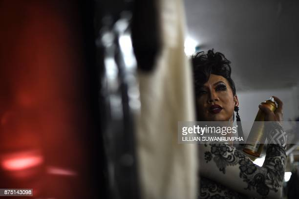 This photo taken on October 7 2017 shows a Thai cabaret performer applying hairspray in the dressing room at ZAG bar a gay entertainment venue in...