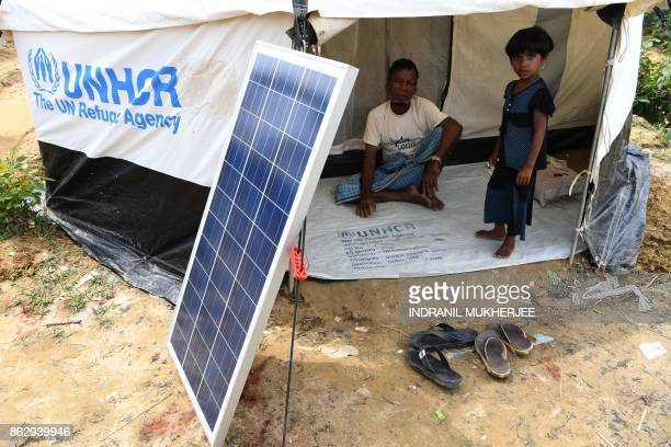 This photo taken on October 7 2017 shows Rohingya refugees waiting for a solar lantern to charge at the Kutupalong refugee camp in Cox's Bazar The...
