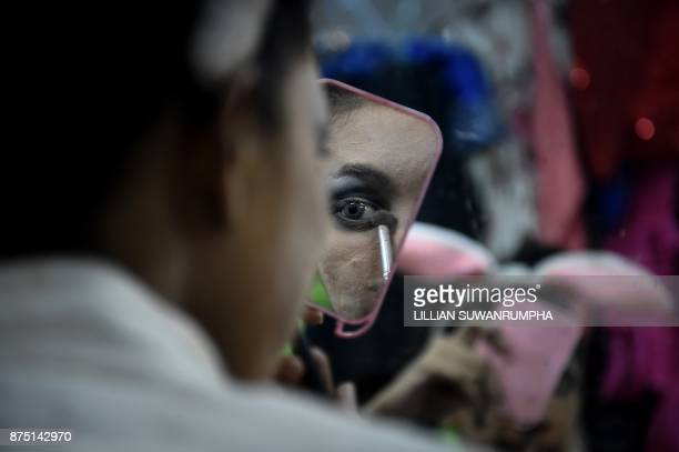 This photo taken on October 8 2017 shows a Thai cabaret performer applying eyeshadow in the dressing room at ZAG bar a gay entertainment venue in...