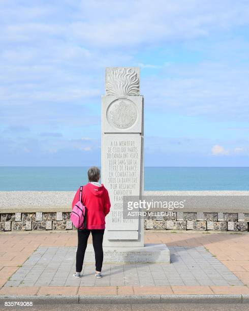 This file photo taken on October 9 2016 in Dieppe shows a woman standing in front of a memorial dedicated to Canadian soldiers during the WWII allied...