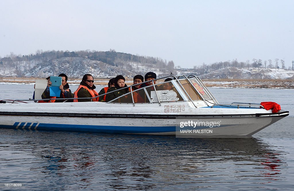 This photo taken on on February 12, 2013, shows Chinese tourists riding a small boat to look at the North Korean border areas near the Chinese town of Dandong. Chinese social media users berated authorities for their relatively mild response to North Korea's nuclear test, with one likening Pyongyang to a 'crazy dog' that had humiliated Beijing. The hostility towards China's defiant neighbour contrasted with the official response from Beijing -- expressing 'firm opposition' but reiterating calls for calm and restraint and not mentioning any reprisals or sanctions. AFP PHOTO/Mark RALSTON