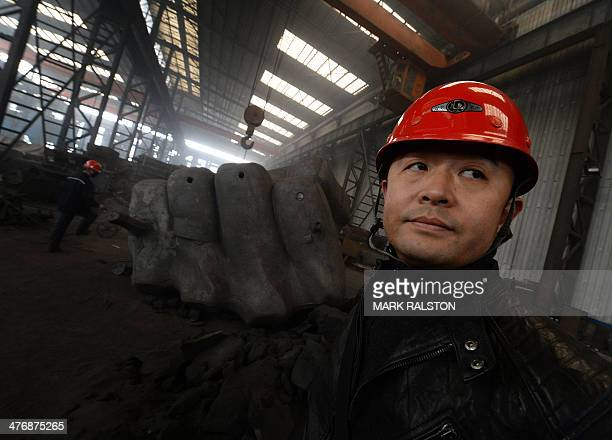 This photo taken on on February 25 2014 shows Chinese Artist Liu Bolin beside one piece of his giant fist sculpture at a steel foundry in Tangshan in...