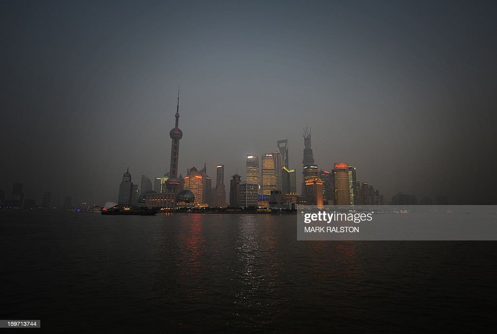 This photo taken on on January 18, 2013 shows the Pudong financial district in Shanghai. Several days of hazardous air quality across large swathes of northern China this week triggered an emergency response which saw schoolchildren kept indoors, factories closed and government cars parked. Experts are urging authorities to take firmer action to confront the consequences of China's rapid industrialisation -- and the spending habits of the middle classes created by its economic boom. AFP PHOTO/Mark RALSTON