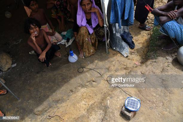 This photo taken on on October 7 2017 shows a Rohingya refugee woman waiting for a solar lantern to charge at the Kutupalong refugee camp in Cox's...