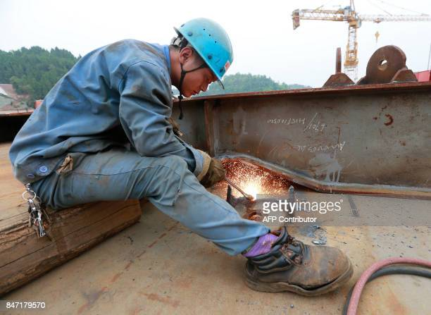 This photo taken on September 14 2017 shows a Chinese emplyee working at the construction of the world's first fullsize replica of the Titanic in...