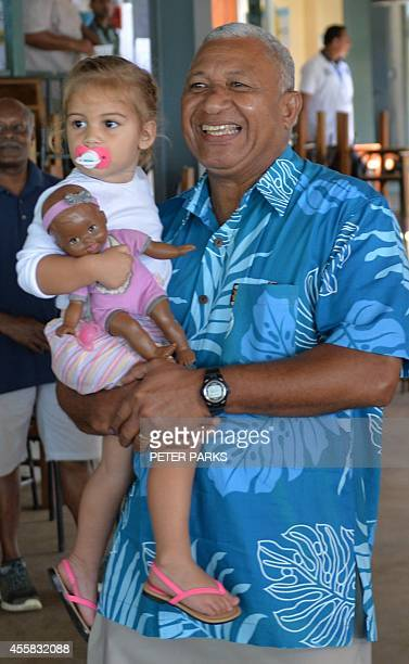 This photo taken on September 17 2014 shows Fiji's military strongman Voreqe Bainimarama carrying his granddaughter after casting his election vote...