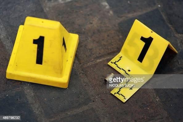 This photo taken on September 24 2015 shows a bullet casing and evidence markers left by forensic investigators of the French police at a crime scene...