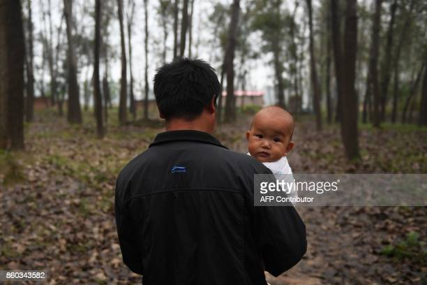 This photo taken on September 27 2017 shows a man carrying a baby to his shack in a village in Lankao in China's central Henan province When...