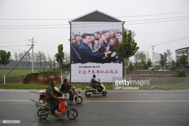 This photo taken on September 27 2017 shows a twostorey high billboard on the side of a house featuring a photo of Chinese President Xi Jinping...