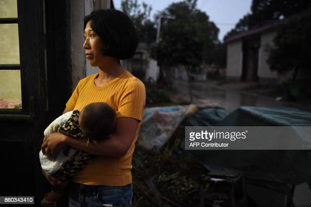 This photo taken on September 27 2017 shows a woman with a baby in a village near the Yellow River in Lankao in China's central Henan province When...