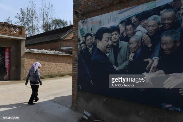 This photo taken on September 28 2017 shows a billboard featuring a photo of China's President Xi Jinping visiting residents in Zhangzhuang village...