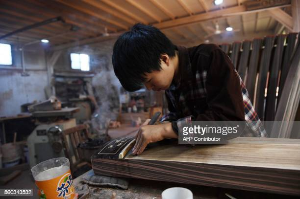 This photo taken on September 28 2017 shows a man making traditional musical instruments in a village in Lankao in China's central Henan province...