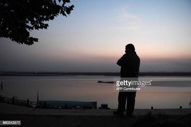 This photo taken on September 28 2017 shows a man resting beside the Yellow River in Lankao in China's central Henan province When President Xi...