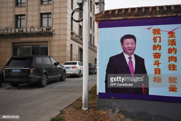This photo taken on September 28 2017 shows a roadside poster of China's President Xi Jinping next to a hotel in Lankao in China's central Henan...