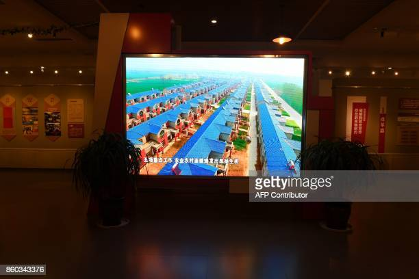 This photo taken on September 28 2017 shows a video screen featuring images of new houses in an exhibition about poverty alleviation at a museum...