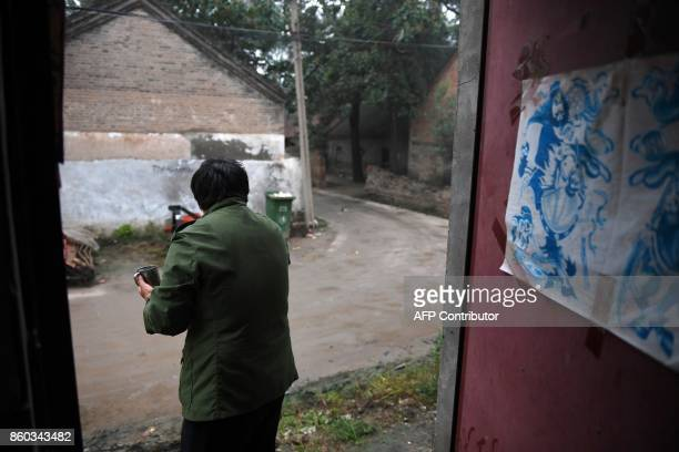This photo taken on September 28 2017 shows a woman brushing her teeth outside her house at a village near the Yellow River in Lankao in China's...