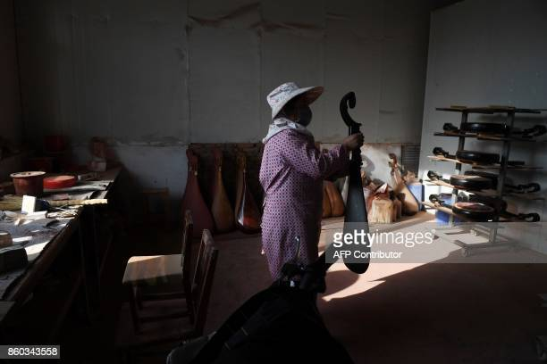 This photo taken on September 28 2017 shows a woman making traditional musical instruments in a village in Lankao in China's central Henan province...