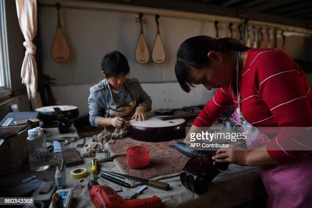 This photo taken on September 28 2017 shows women making traditional musical instruments in a village in Lankao in China's central Henan province...