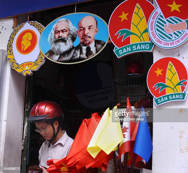 This photo taken on September 29 2010 shows a man walking out of a boutique selling political decorative items including posters with portraits of...