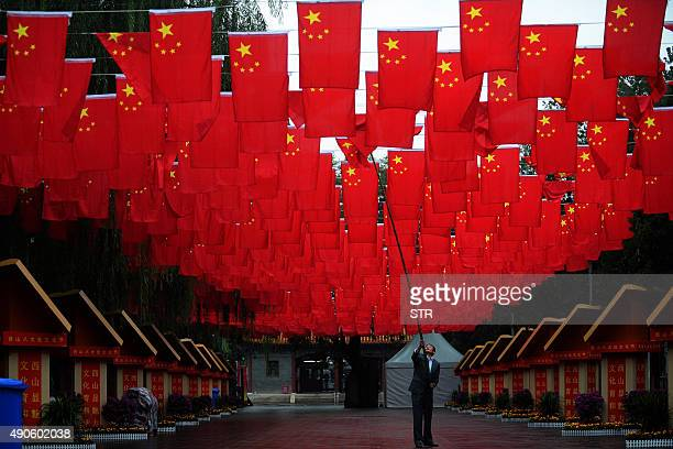 This photo taken on September 29 2015 shows a worker adjusting Chinese national flags following rain at Badachu in Beijing ahead of Chinese National...