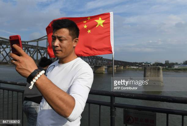 This photo taken on September 5 2017 shows a Chinese visitor taking a selfie with the North Korean city of Sinuiju in the background on the bombed...