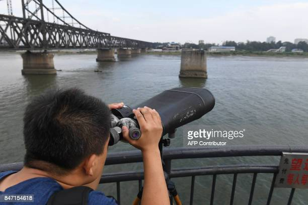 This photo taken on September 5 2017 shows a man looking towards North Korea while visiting the Broken Bridge in the border city of Dandong in...