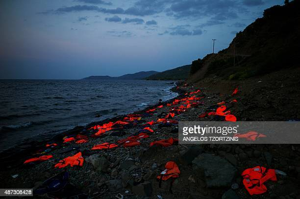 This photo taken on September 8 2015 on the Greek island of Lesbos shows life vests left on the shore by incoming refugees Overwhelmed by the 20000...