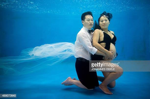 This photo taken on September 9 2014 shows pregnant Chang Yiming and her husband Zhou Guolin posing for underwater pictures at a photo studio in...