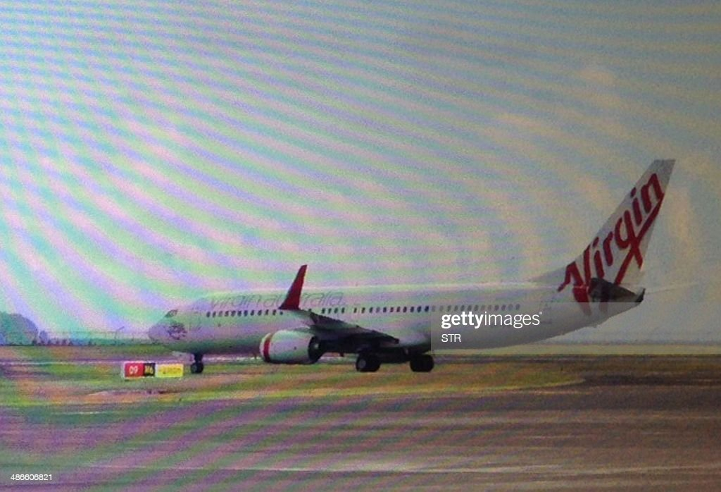 This photo taken through the window of a plane shows a Virgin Australia plane at the centre of a hijacking scare sitting on the tarmac at Bali airport in Denpasar on April 25, 2014. A drunk passenger on a Virgin Australia plane was arrested at Bali airport after triggering a hijack alert when he attempted to enter the cockpit, airline and Indonesian officials said on April 25.
