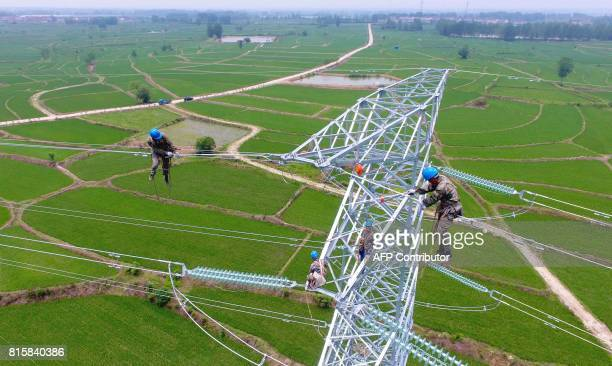 Workers check power lines during maintenance work in Laian in China's eastern Anhui province on July 17 2017 China posted betterthanexpected growth...