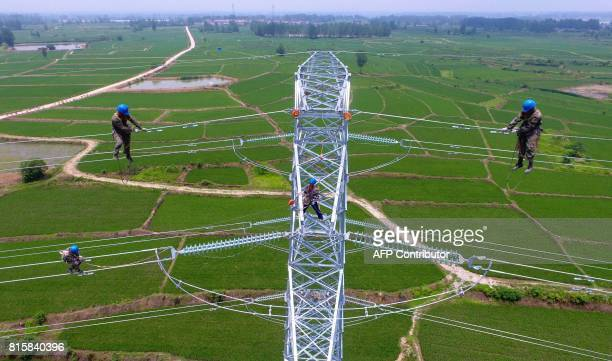 TOPSHOT Workers check power lines during maintenance work in Laian in China's eastern Anhui province on July 17 2017 China posted betterthanexpected...