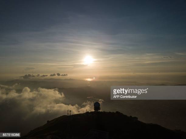 This photo taken with a drone on August 5 2017 shows the Hong Kong Observatory radar station silhouetted on the top of Tai Mo Shan Hong Kong's...