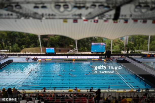 TOPSHOT This photo taken with a tilt and shift lens shows Singapore and Philippines players competing during their men's water polo round match at...