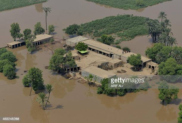 This photograph taken from a Pakistan army helicopter shows an aerial view of residents at their houses surrounded by floodwaters in the flooded area...