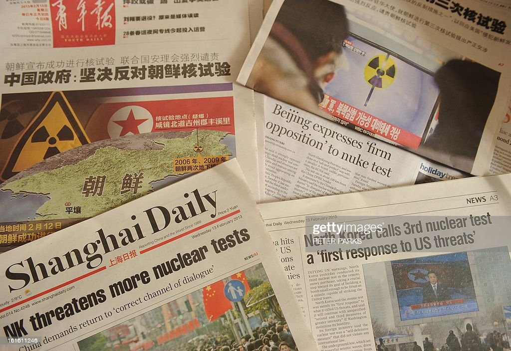 This photograph taken in Shanghai on February 13, 2013 shows the reaction to North Korea's nuclear test on pages of some Chinese newspapers. Chinese social media users berated authorities for their relatively mild response to North Korea's widely condemned nuclear test, likening Pyongyang to a 'crazy dog' that had humiliated Beijing. AFP PHOTO/Peter PARKS