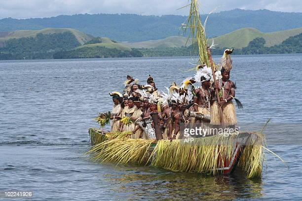 This photograph taken June 19 2010 shows Papuan tribes people dressed as warriors sailing on Senatani Lake aboard a ceremonial boat during the annual...