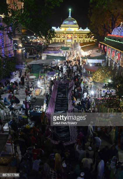 This photograph taken late March 24 shows a general view as Indian Muslims carry a large chaddar or shawl at The ShahEAlam Roja in Ahmedabad during...