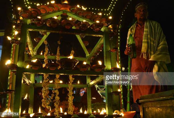 This photograph taken late March 24 shows an Indian Muslim custodian beside a rack of lit oil lamps at The ShahEAlam Roja in Ahmedabad during the...