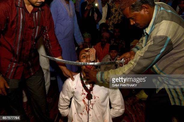 This photograph taken late March 24 shows an Indian Muslim having his tongue cut during 'Rafai Silsila' at The ShahEAlam Roja in Ahmedabad during the...