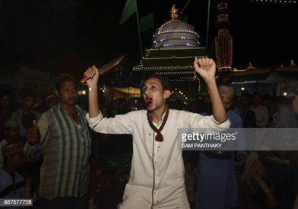This photograph taken late March 24 shows an Indian Muslim with his tongue bleeding during 'Rafai Silsila' at The ShahEAlam Roja in Ahmedabad during...