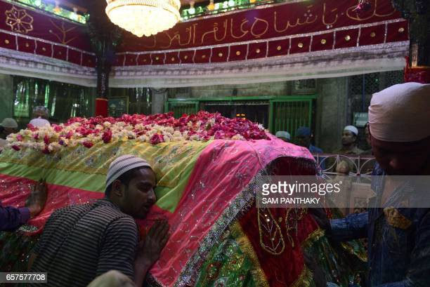 This photograph taken late March 24 shows Indian Muslims as they pay their respects at the tomb at The ShahEAlam Roja in Ahmedabad during the marking...