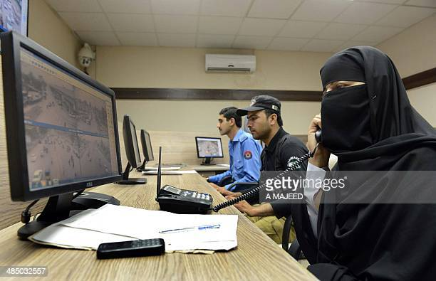 This photograph taken on April 15 2014 shows Pakistani police officials monitoring screens showing live video footage of different parts of Peshawar...