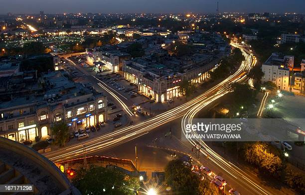 This photograph taken on April 18 2013 shows the Indian capital's skyline as traffic drives around the outer circle of Connaught Place in the heart...
