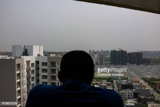 This photograph taken on April 27 an Indian man looks out onto incomplete residential apartments in Greater Noida some 25 kilometres southeast of New...