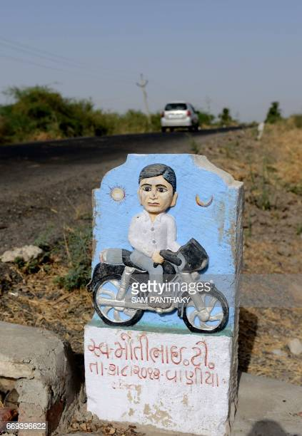 This photograph taken on April 7 shows a ' Paliya' or memorial milestone of the late Motibhai T seated on his motorcycle on the roadside in The...