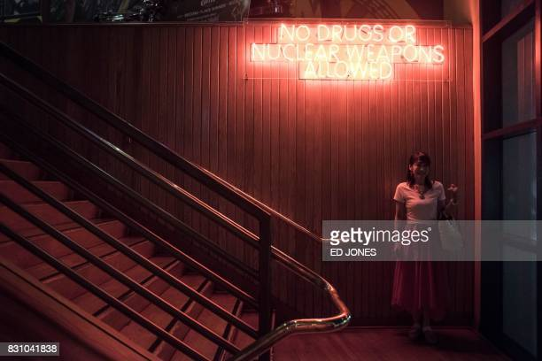 TOPSHOT This photograph taken on August 12 shows a woman posing for a friend beneath a sign reading 'No drugs or nuclear weapons allowed' at the...
