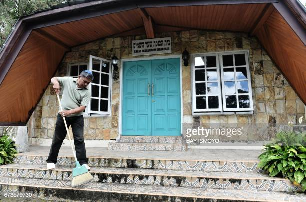 This photograph taken on February 17 2017 shows a member of Indonesia's Jewish community sweeping the steps to the synagogue ahead of a prayer...